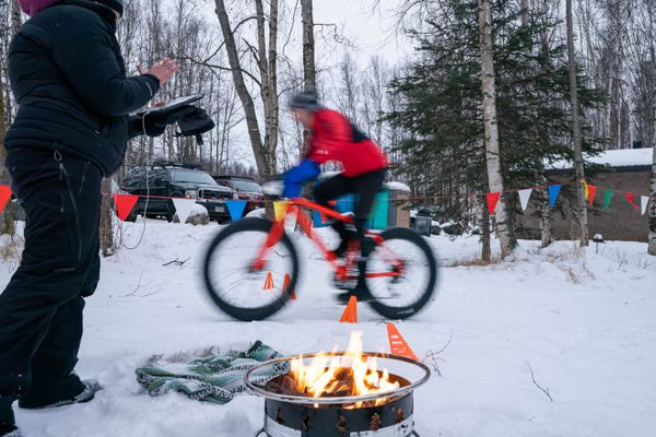 A rider crosses the finish line during the Merry Masher fat bike race on Saturday, Dec. 26, 2020 at Mirror Lake in Chugiak. (Loren Holmes / ADN)