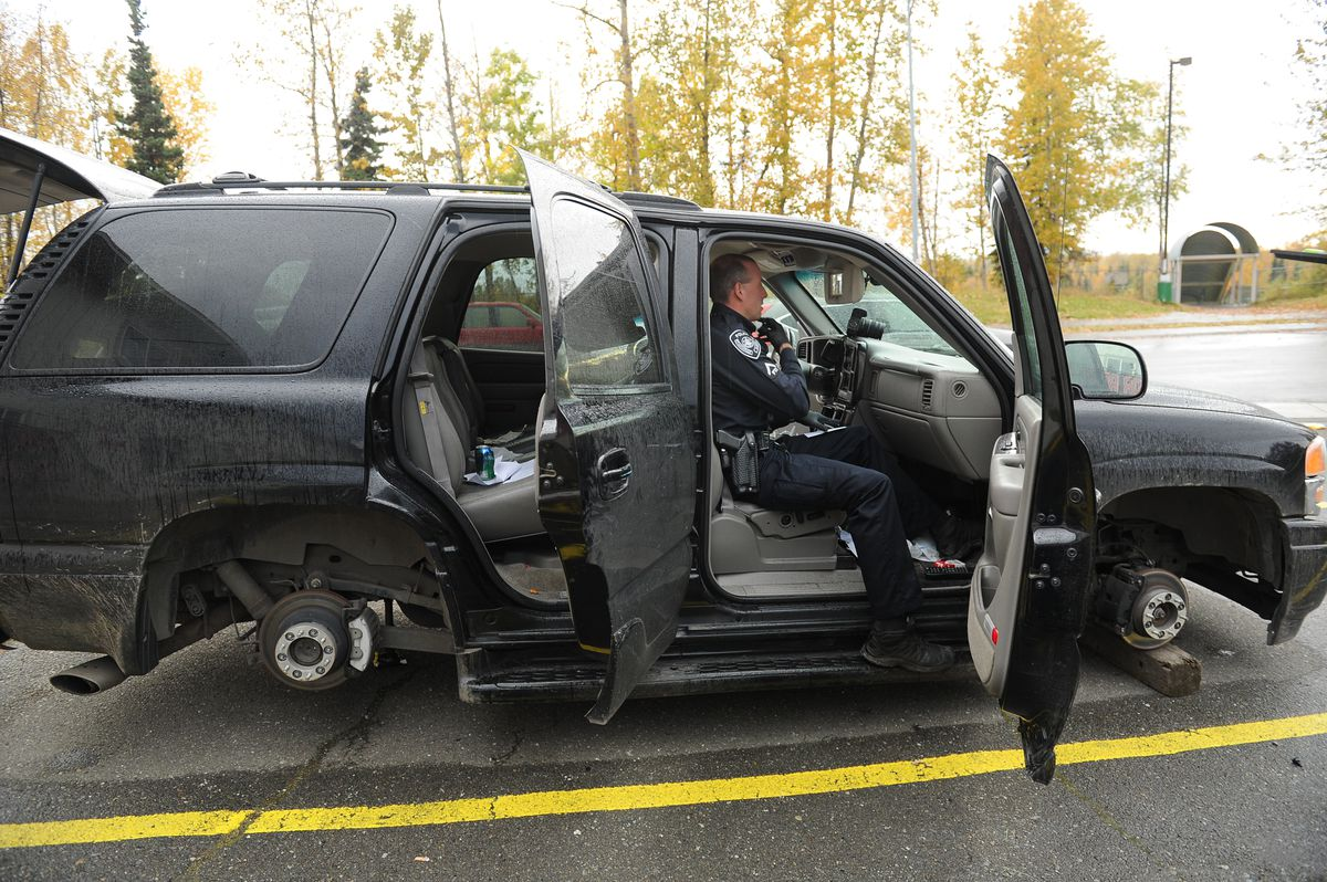 Anchorage Police Department officer Shawn Davies processes a stolen vehicle in the Mountain View neighborhood of Anchorage, Alaska on Wednesday, Sept. 27, 2017. (Bob Hallinen / ADN)