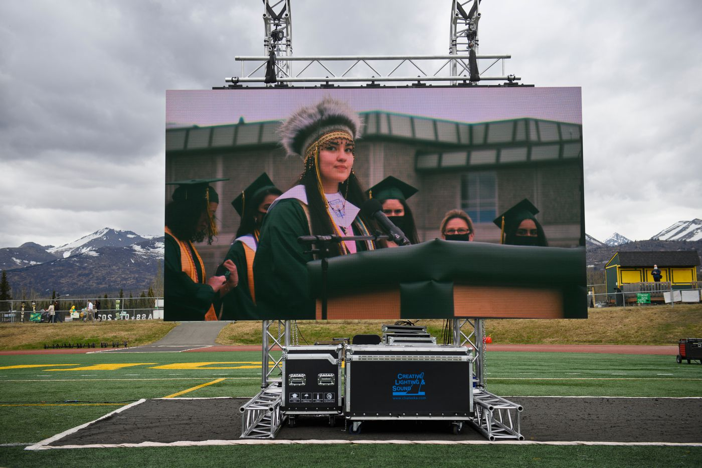 Wearing her Yup'ik headdress, Nyché Andre gives a land acknowledgement at the start of the Service High School graduation on May 12, 2021. Her image is shown on a video screen at the side of the stage. (Marc Lester / ADN)