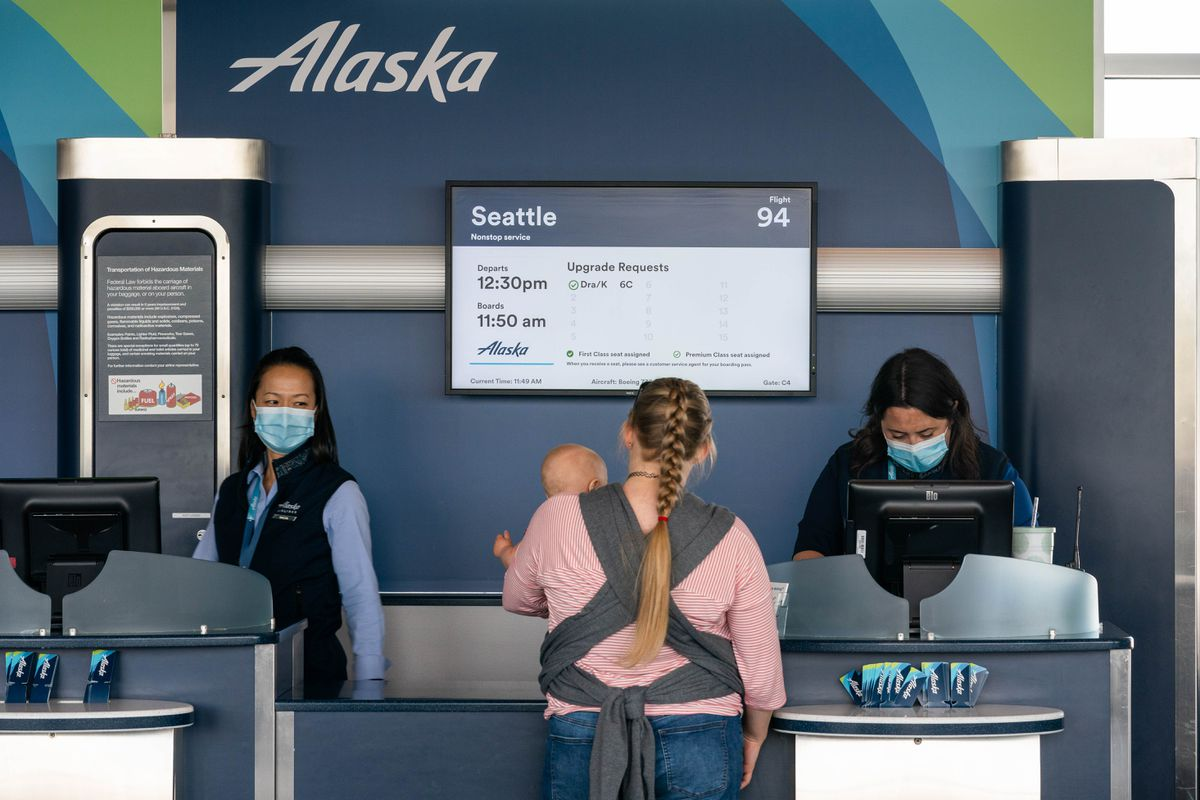 Alaska Airlines employees Sachi Kwon, left, and Mary Graham help a customer at the Ted Stevens Anchorage International Airport on Friday, June 5, 2020. (Loren Holmes / ADN)