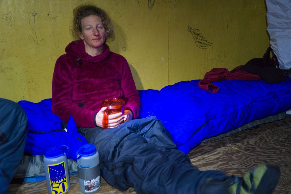 Robin Beebee relaxes in the shelter cabin between Ambler and Kiana after a long day of skiing. This was the only night the group did not sleep in a house or school. (Seth Adams)