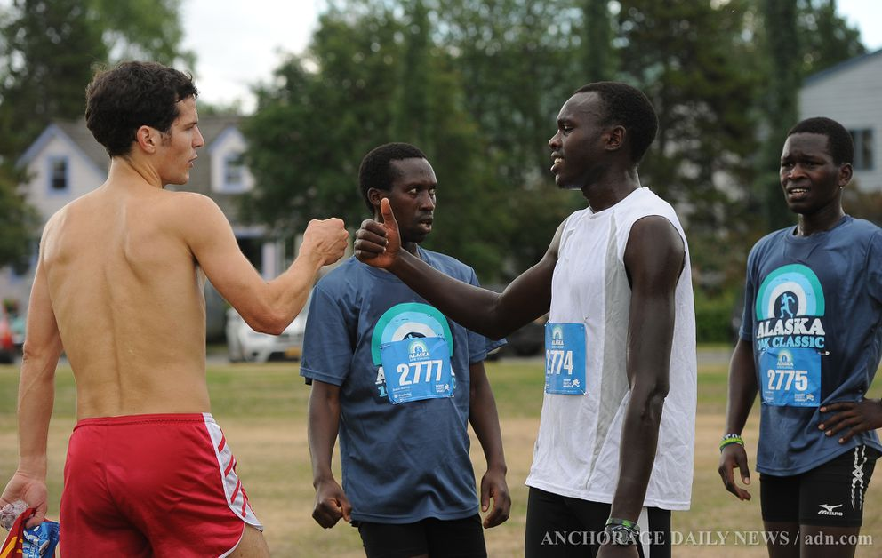 Tony Tomsich, left, bumps fists with Isaac Kangogo after the 2013 Alaska 10K Classic. (ADN archives)
