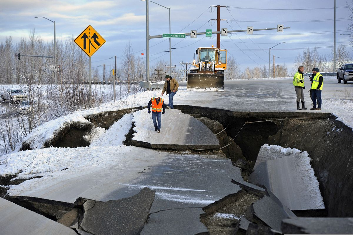 FILE - In this Friday, Nov. 30, 2018 file photo, workers inspect a road that collapsed during an earthquake in Anchorage, Alaska. The collapsed roadway that became an iconic image of the destructive force of a magnitude 7.0 earthquake and its aftershocks was repaired just days after the quake. The off-ramp connecting Minnesota Drive and Ted Stevens Anchorage International Airport reopened Tuesday, Dec. 4, 2018, with shoulder work completed Wednesday. (AP Photo/Mike Dinneen, File)