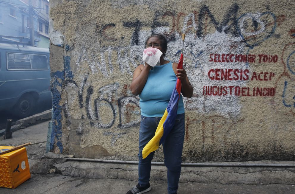 An anti-government protester affected by tear gas, fired by security forces, holds a Venezuelan flag during a show of support for an apparent mutiny by a national guard unit in the Cotiza neighborhood of Caracas, Venezuela, Monday, Jan. 21, 2019. (AP Photo/Ariana Cubillos)
