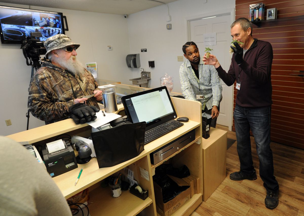 Owner Bryant Thorp, right, holds immature cannabis plants for approval from first customer Butch Gilmer, left, while employee Stanley Nero holds open a pouch as Arctic Herbery opens for business midday Friday. (Erik Hill / Alaska Dispatch News)