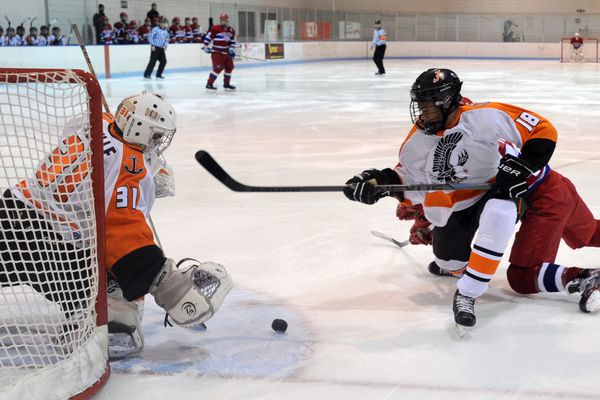 ERIK HILL / Alaska Dispatch News West goaltender Isaiah Saville, left, and teammate Cyril Boots stop an East scoring chance during first-period action on Tuesday evening, December 8, 2015, at Ben Boeke Ice Arena.