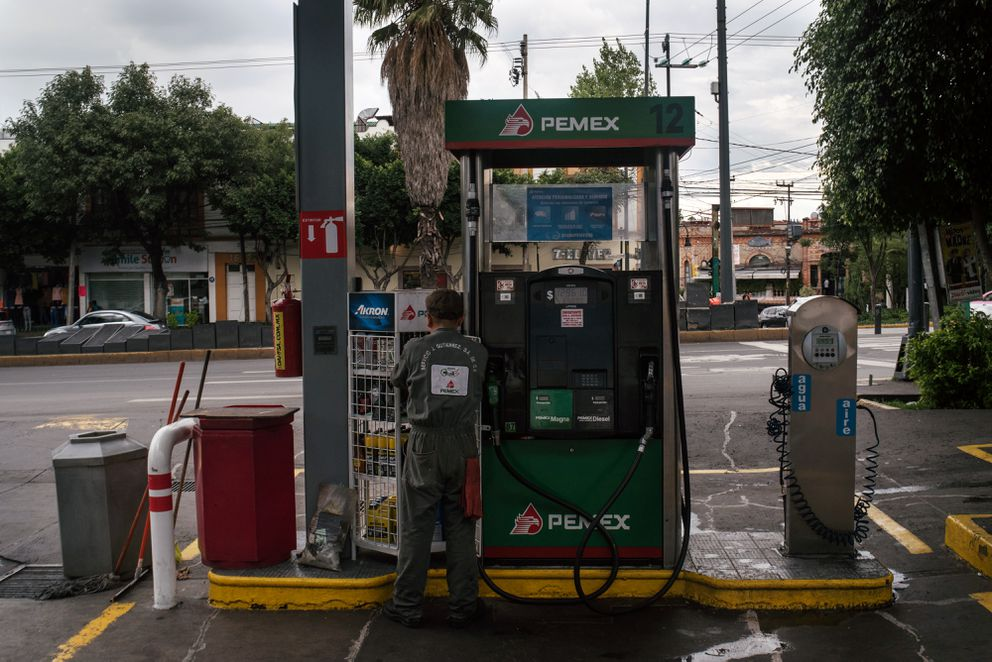 An attendant stands next to a fuel pump at a Petroleos Mexicanos (Pemex) gas station in Mexico City on Aug. 6, 2018. Bloomberg photo by Luis Antonio Rojas.
