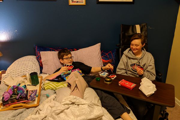 Hank Martiny, 10, left, and his sister Maddy, 14, play a card game at their Eagle River home. The siblings were seriously injured when they were hit by a car driven by an alleged drunk driver while they were riding their bicycles on an Eagle River sidewalk on March 24, 2019. (Photo by Gillian Martiny / Courtesy)