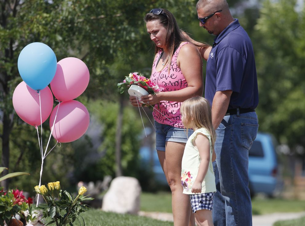 Ashley Bell, left, is consoled by her husband, Steven, and 4-year-old daughter Liberty as the woman places a tribute outside the home where a pregnant woman and her two daughters lived Thursday, Aug. 16, 2018, in Frederick, Colo. (AP Photo/David Zalubowski)