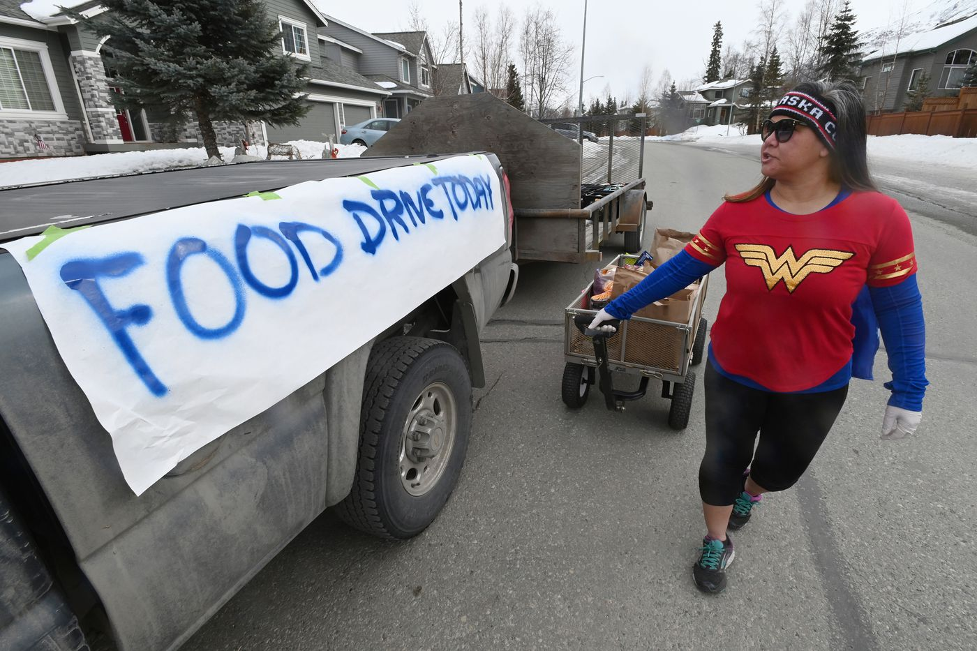 Pheng Scott pulled a cart wearing a Wonder Woman shirt and a cape as she helped collect donated food by her neighbors in the Eagle Pointe subdivision nestled behind Eagle River High School on Wednesday, April 1, 2020. (Bill Roth / ADN)