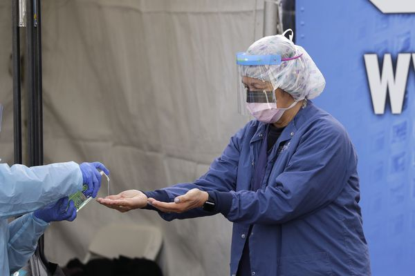In this March 17, 2020, photo, Theresa Malijan, a registered nurse, has hand sanitizer applied on her hands after removing her gloves after she took a nasopharyngeal swab from a patient at a drive-through COVID-19 testing station for University of Washington Medicine patients in Seattle. The Associated Press has found that the critical shortage of testing swabs, protective masks, surgical gowns and hand sanitizer can be tied to a sudden drop in imports of medical supplies. (AP Photo/Elaine Thompson)