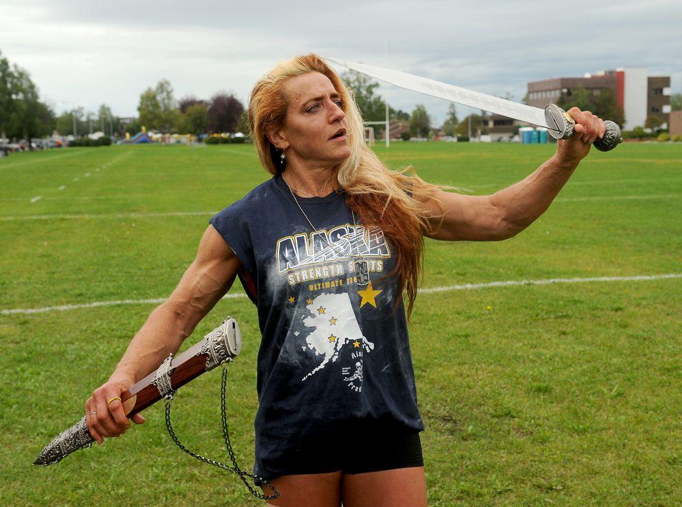 Adrienne Schenfele wields the gladiatorsword she won at the Alaska Strongman Championships. (Bob Hallinen / Alaska Dispatch News)