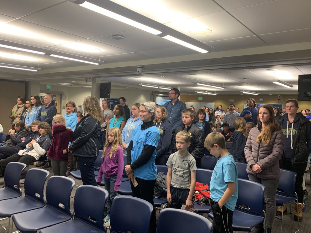 Aquarian Charter School advocates stand at the Anchorage School Board meeting on Tuesday to show their support for adding funding for a new roof and other projects at the school to the bond proposal. (Tegan Hanlon / ADN)