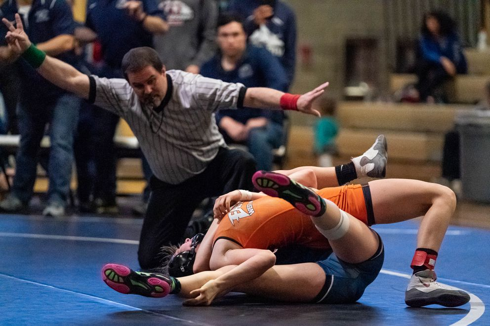 West's Carson Adams tries to pin Eagle River's Ashley Andrews in the girls 112-pound final. Andrews went on to win the match. (Loren Holmes / ADN)