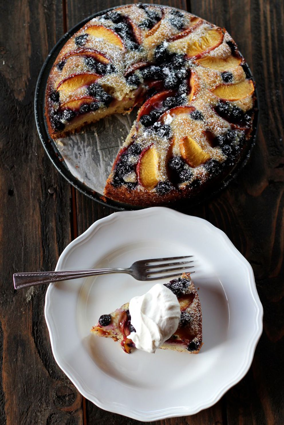 With a dusting of powdered sugar and a dollop of freshly whipped cream, this blueberry nectarine cake is ready to enjoy. (Maya Wilson / Alaska from Scratch)