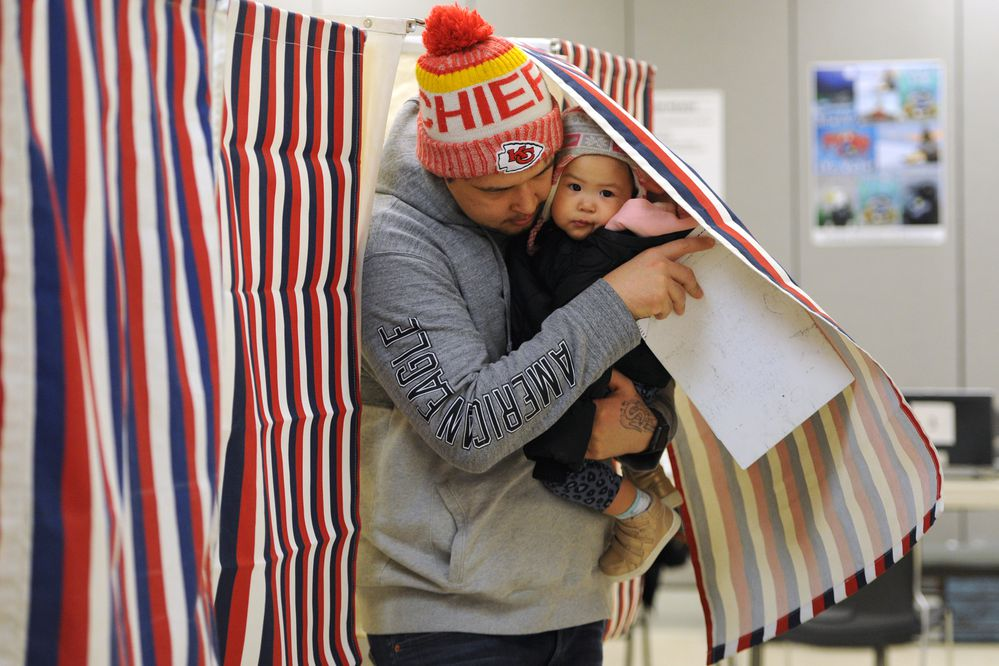 Radley Christiansen holds his almost one-year-old daughter Alana while exiting a voting booth at the Region II Elections office on Election Day, Tuesday, Nov. 6, 2018. (Bill Roth / ADN)