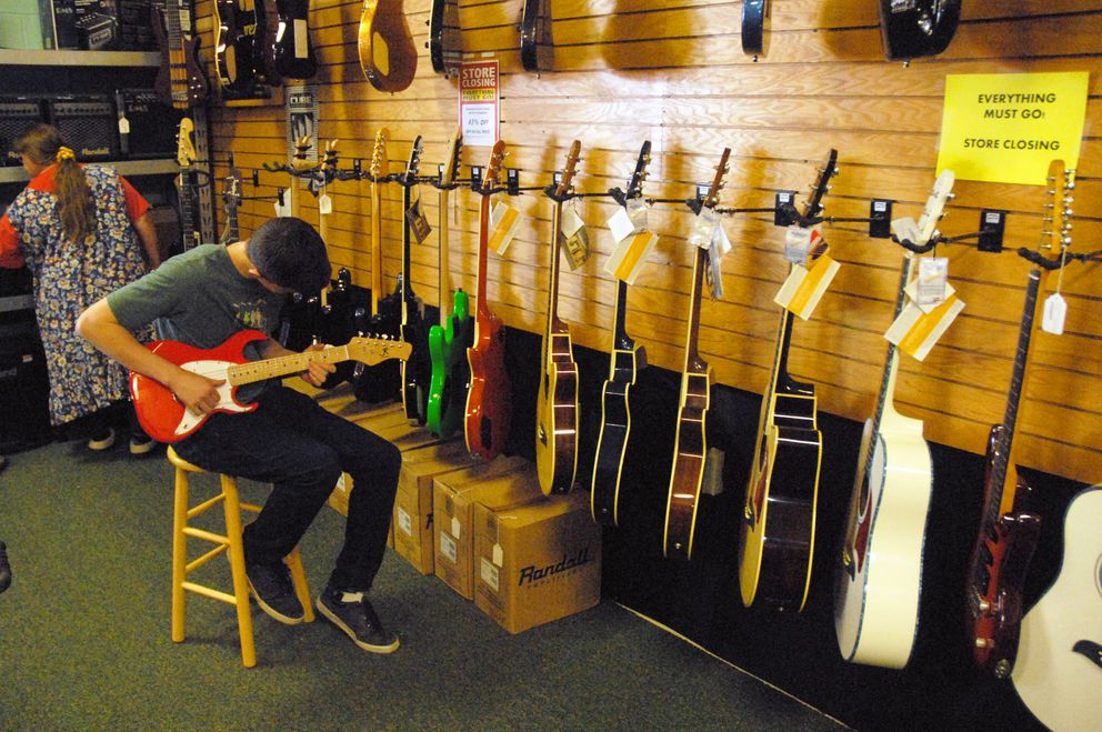 Sam Weber plays a guitar at Mike's Music in Eagle River on Monday, June 3, 2019. The store is closing after 25 years, according to owner Sharon Dunckle. (Matt Tunseth / Chugiak-Eagle River Star)