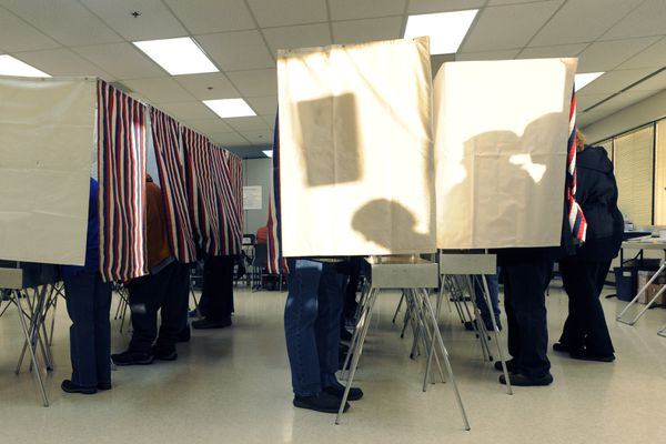 People waiting to vote cast shadows on booths on the first day of early voting at the Division of Elections office at 2525 Gambell Street on Monday morning, Oct. 24, 2016, in Midtown. (Erik Hill / Alaska Dispatch News)