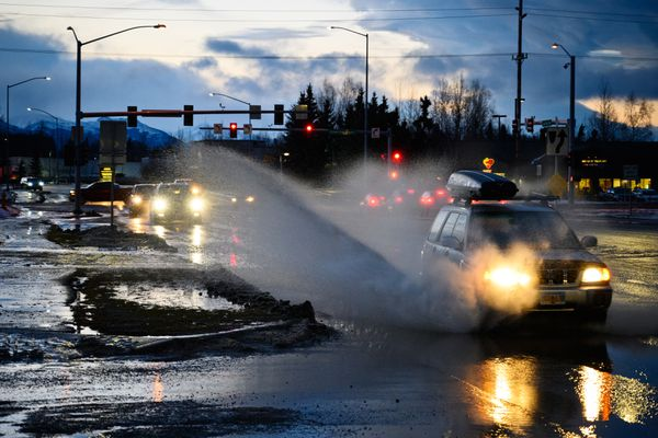 Vehicles travel through standing water on Lake Otis Parkway near Dowling Road on an unusually warm day on December 31, 2019. (Marc Lester / ADN)