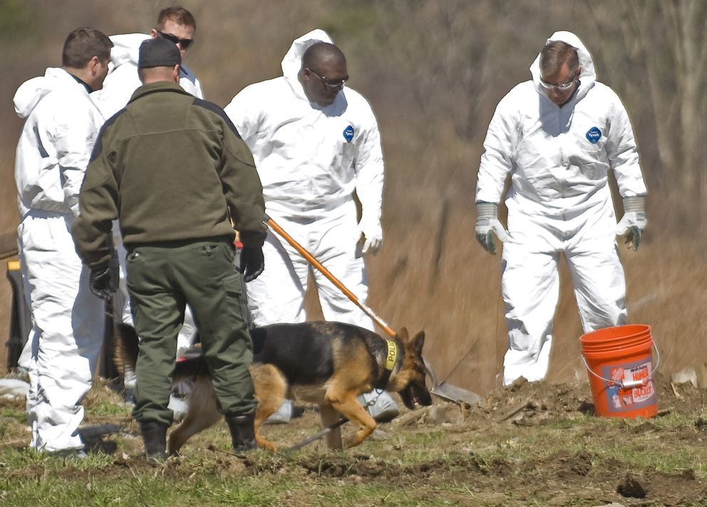 Vermont State Police investigators pause to allow a dog to inspect dirt and debris at a dig site off Vermont 15 near Lang Farm in Essex, Vt., Thursday, April 12, 2012, in what Essex Police Chief Brad LaRose described as part of the ongoing investigation into the disappearance of William and Lorraine Currier. Israel Keyes confessed to killing the Curriers. (Ryan Mercer / Burlington Free Press)