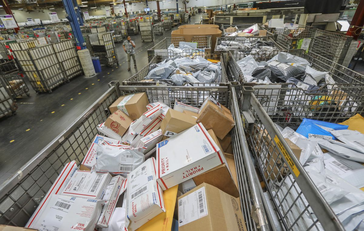 Postal workers sort parcels at Margaret L. Sellers Processing and Distribution Center at the USPS Carmel Mountain Post Office on May 14, 2020 in San Diego, California. The post office is seeing a huge increase in the amount of packages its handling. (Eduardo Contreras/The San Diego Union-Tribune/TNS)