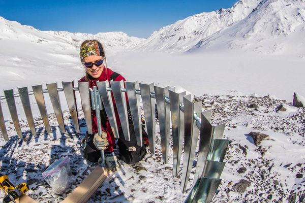 UAF researcher Anna Liljedahl puts up a wind shield around a gauge that she installed on Jarvis Glacier to measure rainfall in 2013. Jarvis Glacier is in the Alaska Range south of Delta Junction. (Todd Paris / UAF)
