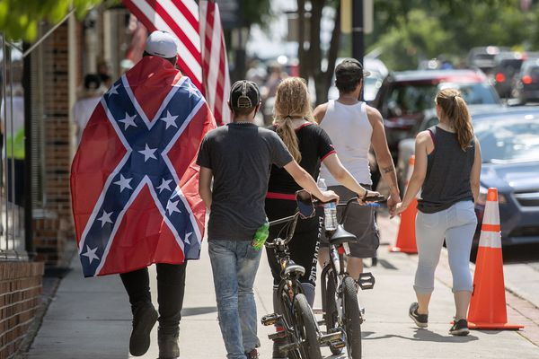 FILE - In this July 3, 2020, file photo a man wears a Confederate flag while walking with others in Marion, Va. Defense leaders are weighing a new policy that would bar the display of the Confederate flag at department facilities without actually mentioning its name, several U.S. officials said Thursday, July 16. Officials said the new plan presents a creative way to ban the Confederate flag in a manner that may not raise the ire of President Donald Trump, who has defended people's rights to display it. (Andre Teague/Bristol Herald Courier via AP, File)
