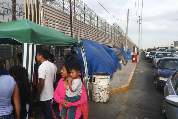 In this May 5, 2019 photo, migrants walk between tents, left, and cars waiting to cross the border in San Luis Rio Colorado, Mexico, and Arizona. The tent slots are for families about to be called, allowing them to be ready on a moment's notice. (AP Photo/Elliot Spagat)