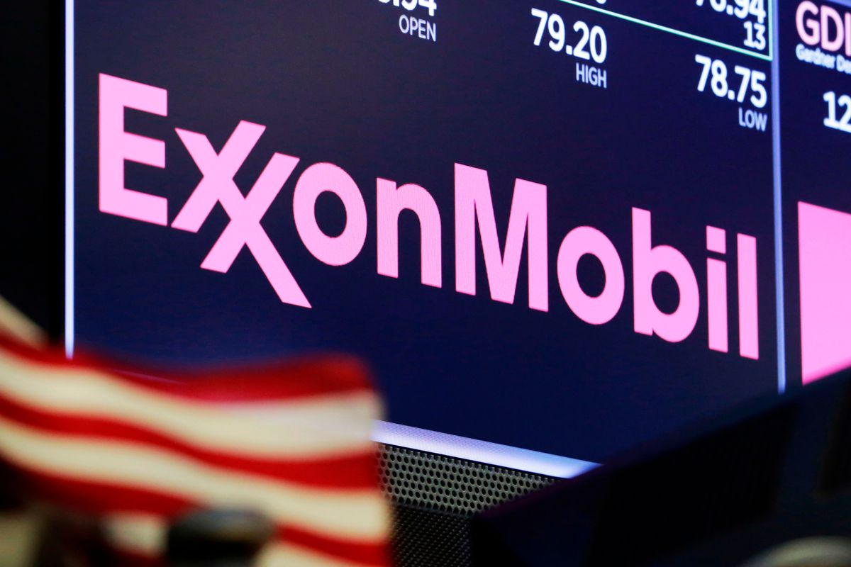 FILE - In this April 23, 2018, file photo, the logo for ExxonMobil appears above a trading post on the floor of the New York Stock Exchange. Exxon Mobil is facing a major challenge from a group of investors in one of the biggest fights a corporate boardroom has faced over its stance on climate change, an issue of rising urgency among many shareholders. The investor group is pushing to replace four of the oil giant's board members with executives who they say are better suited to make money and to lead the company through a transition to cleaner energy. (AP Photo/Richard Drew, File)