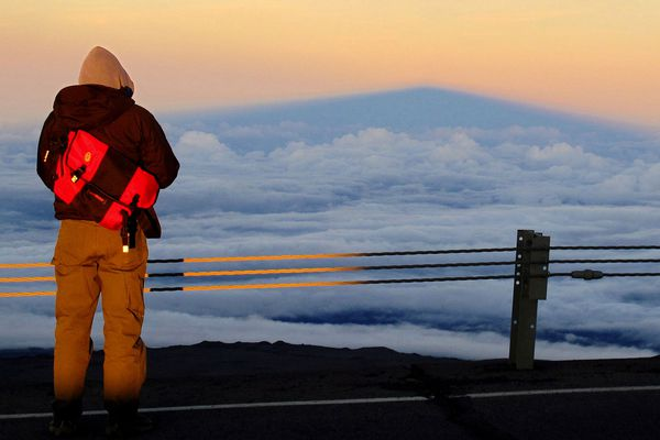 A summit visitor looks eastward to the shadow of Hawaii's Mauna Kea cast against clouds at sunset in June 2012. (Brian J. Cantwell/Seattle Times/TNS)