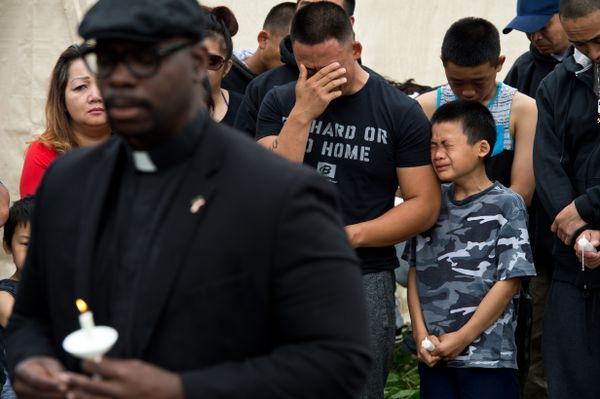 Emotion overtakes family members as a prayer is offered. (Marc Lester / ADN)