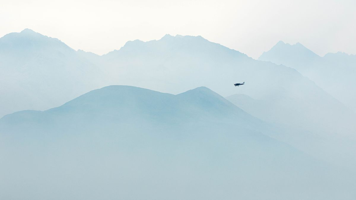 A small airplane approaches Merrill Field in front of smoke-obscured mountains Tuesday, Aug. 20, 2019. (Loren Holmes / ADN)