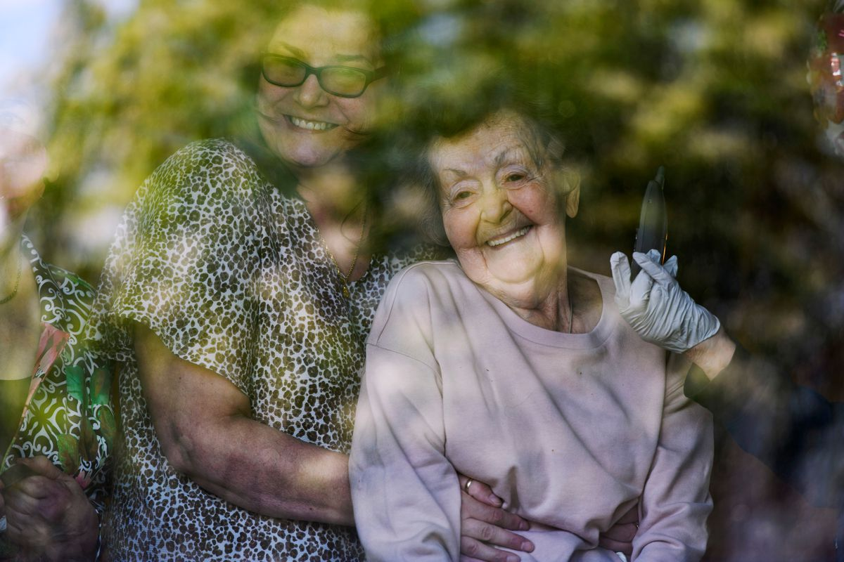 Marge Tomsic, right, watches as friends sing outside her home on June 12, 2020. Caregiver Sarah Powell is at left. The gathering was to celebrate Tomsic's 98th birthday from a coronavirus-safe distance. (Marc Lester / ADN)