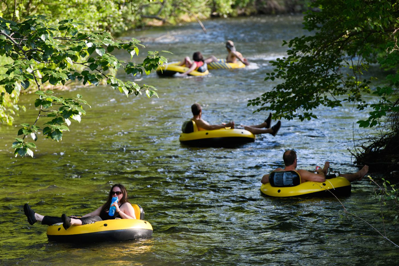 A group of inner tubers float through a residential neighborhood west of Lake Otis Parkway on July 5. (Marc Lester / ADN)