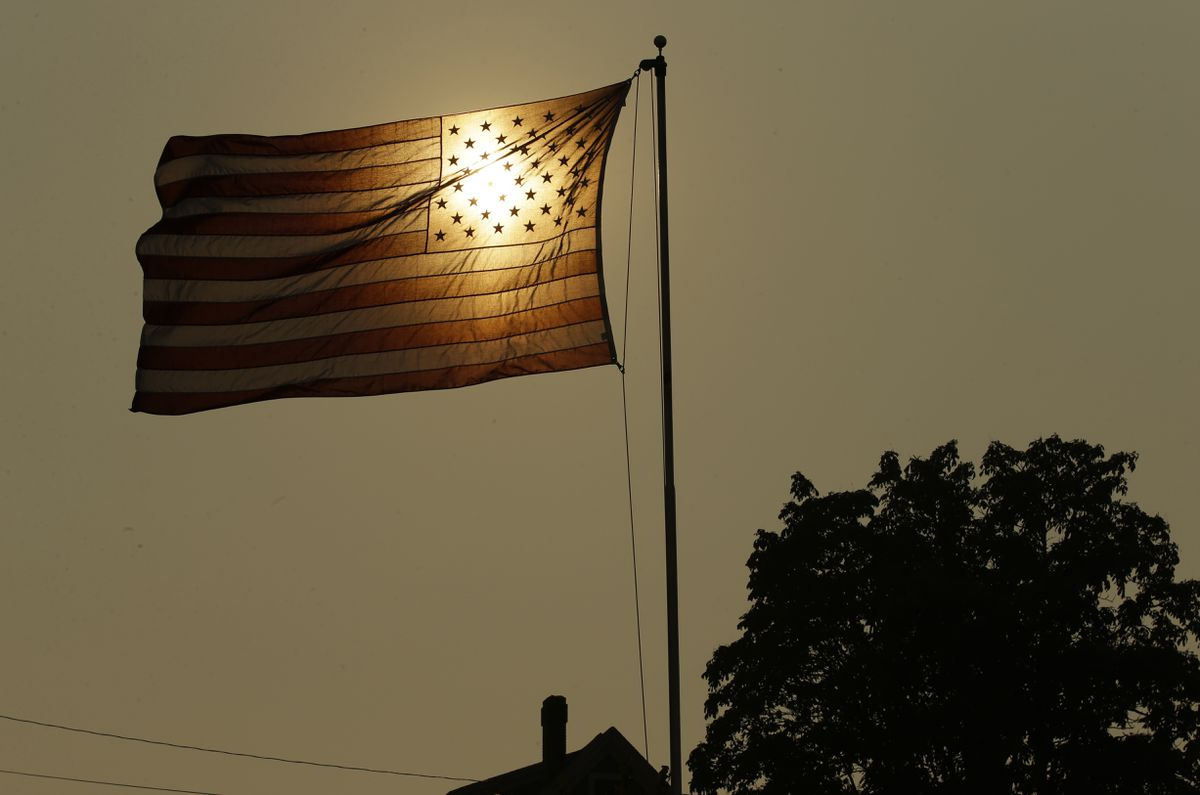 FILE - In this Aug. 2, 2017 file photo, the evening sun shines through a U.S. flag flying in the wind in Tacoma, Wash., against a sky made hazy with smoke from wildfires. (AP Photo/Ted S. Warren, File)