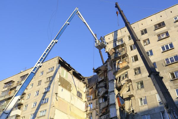 Emergency Situations employees working at the scene of a collapsed apartment building in Magnitogorsk, a city of 400,000 people, about 1,400 kilometers (870 miles) southeast of Moscow, Russia, Monday, Dec. 31, 2018. Russian emergency officials say that at least four people have died after sections of the apartment building collapsed after an apparent gas explosion in the Ural Mountains region. (AP Photo/Maxim Shmakov)