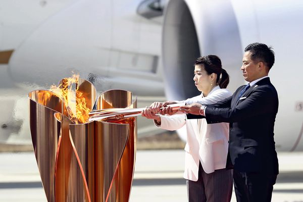 Wrestler Saori Yoshida, left, and judoka Tadahiro Nomura, both three-time Olympic champions, light the torch from the Olympic flame in Higashi-Matsushima, Miyagi Prefecture, on March 20, 2020 after it arrived on a chartered flight from Greece. MUST CREDIT: Japan News-Yomiuri