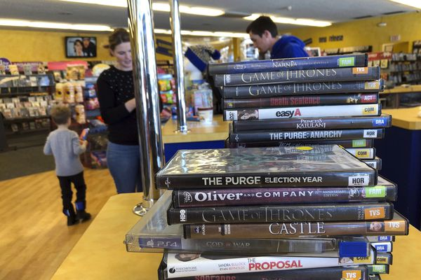 Returned movies wait to be shelved at the last Blockbuster on the planet in Bend, Ore., on Monday, March 11, 2019 as a customer checks out movies in the background. When a Blockbuster in Perth, Australia, shuts its doors for the last time on March 31, the store in Bend, Ore., will be the only one left on Earth, and most likely in the universe. (AP Photo/Gillian Flaccus)