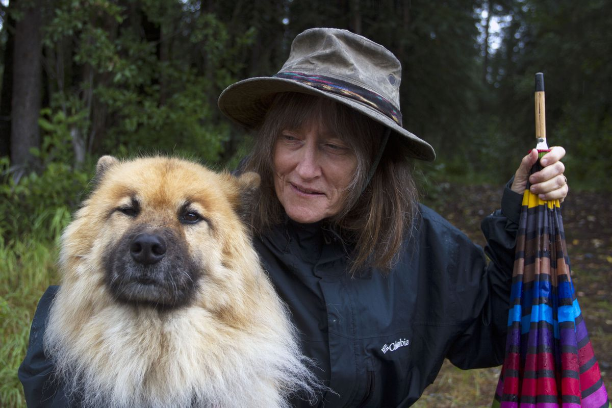 """Beloved children's book author and illustrator Shannon Cartwright, with her dogCoda, near Talkeetna. Cartwright's new book, """"Alaska Animals, You and I"""", is written for preschoolers. Critic David James says """"the artwork is beautifully accurate without being overwhelmingly detailed."""" (Sarah Bell / Alaska Dispatch News)"""