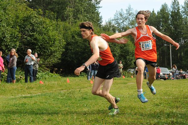 Declan Dammeryer gets the tag off from West High teammate Ethan Davis as he starts the anchor leg of the Steel Bucket Relay at Kincaid Park in Anchorage, Alaska, on Tuesday August 15, 2017. The team went on to win the race. (Bob Hallinen / Alaska Dispatch News)
