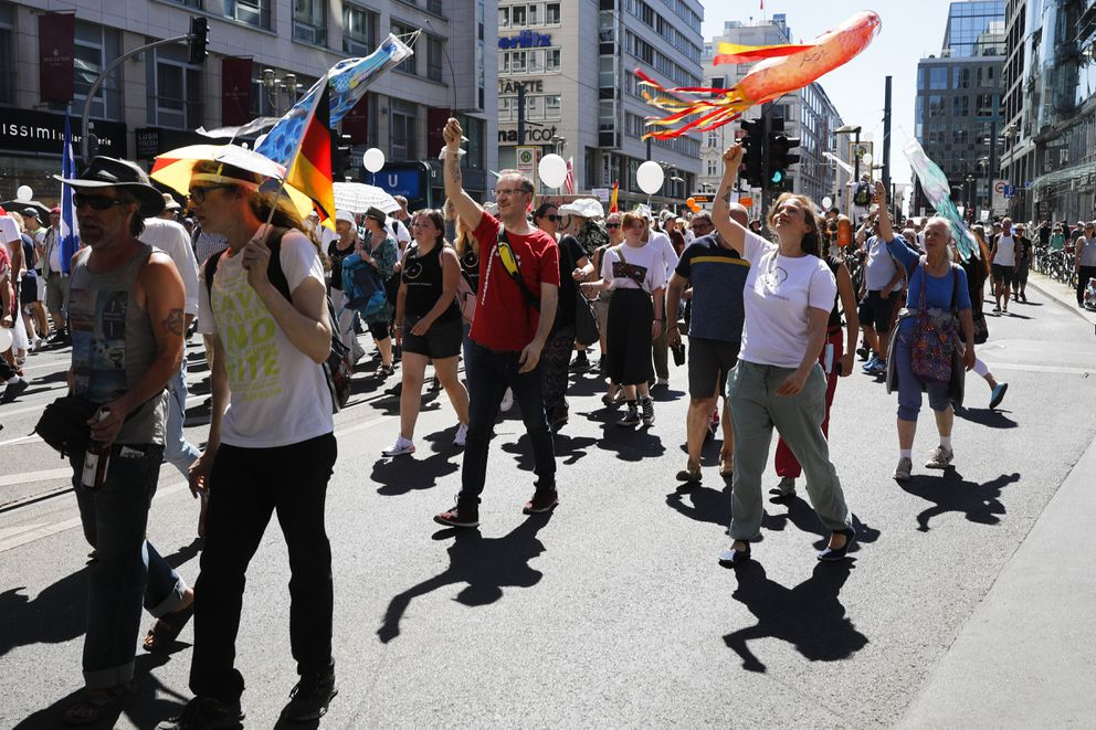 People mostly without face masks attend a demonstration with the slogan 'The end of the pandemic - freedom day ' - against coronavirus restrictions in Berlin, Germany, Saturday, Aug. 1, 2020. It comes amid increasing concern about an upturn in infections in Germany. (AP Photo/Markus Schreiber)