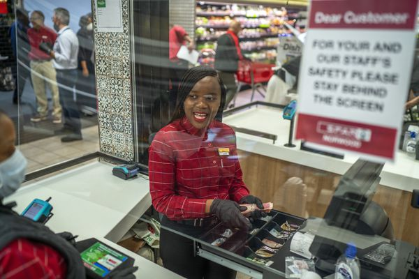 In this March 30, 2020, photo, Zandile Mlotshwa, 21, cashier at Spar supermarket in the Norwood suburb of Johannesburg, counts her cash at the end of her shift. From South Africa to Italy to the U.S., grocery workers — many in low-wage jobs — are manning the front lines amid worldwide lockdowns, their work deemed essential to keep food and critical goods flowing. (AP Photo/Jerome Delay)