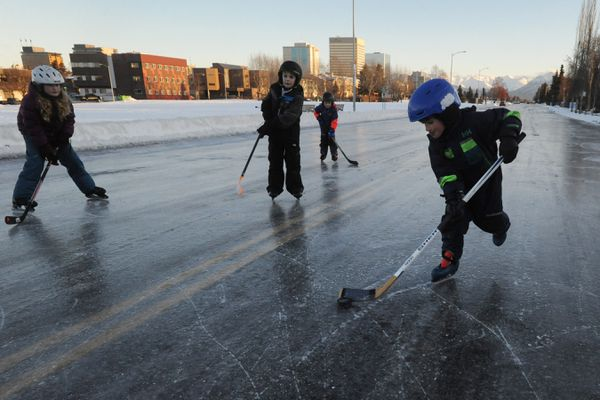 Mackey Cohen, 7, carries the puck near the double yellow line on 10th Avenue as skaters took to the icy streets near downtown Anchorage on Sunday, Dec. 8, 2019. (Bill Roth / ADN)
