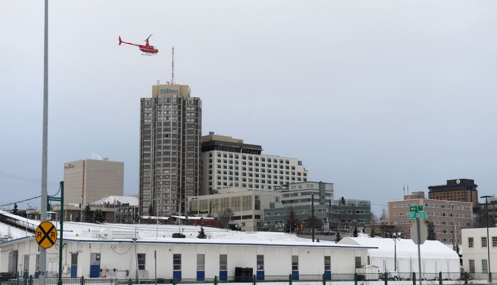 A helicopter passes over the Ship Creek area with the Hilton Hotel in the background after a 7.0 earthquake in Anchorage, AK on Friday, Nov. 30, 2018. (Bob Hallinen / ADN)