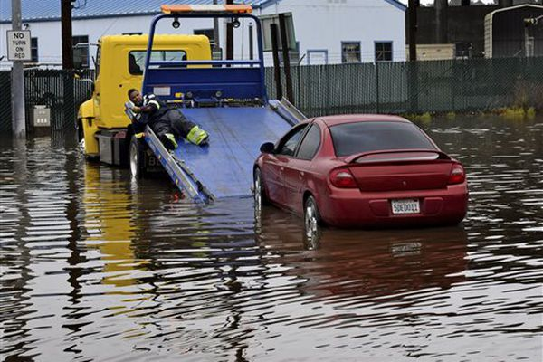 A tow driver attempts to retrieve a stalled car at a flooded park and ride lot on Tuesday, Dec. 22, 2015, in Mill Valley, Calif. A weather pattern that could be associated with El Nino has turned winter upside-down across the U.S. during a week of heavy holiday travel, bringing spring-like warmth to the Northeast, a risk of tornadoes in the South and so much snow in parts of the West that there are concerns about avalanches.