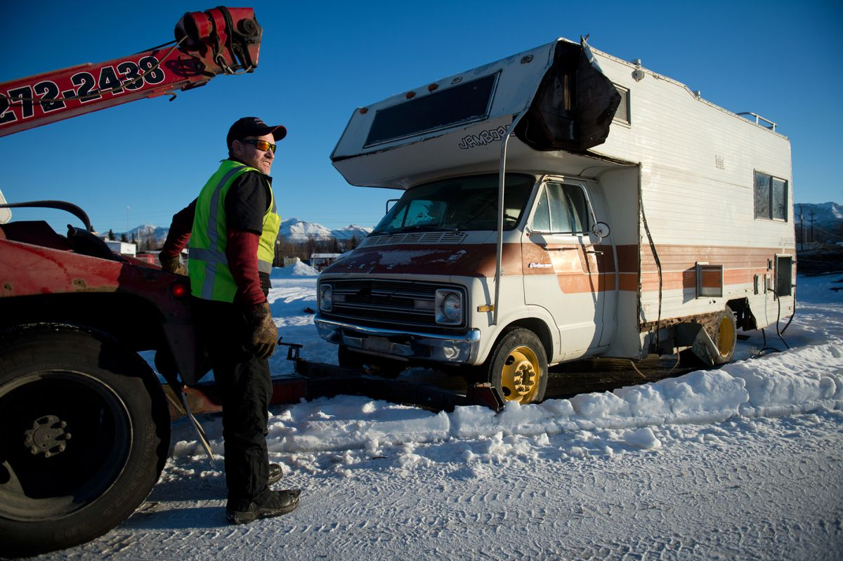 Gordon Bailey, of Alaska Towing and Wrecking, prepares to tow a recreational vehicle from South Gambell Street near Klatt Road on January 15, 2019. The vehicle was one of several that the company tows each day as part of its contract with the city to remove abandoned vehicles. (Marc Lester / ADN)