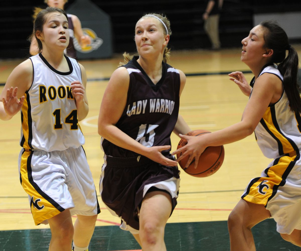 Vera Fefelov of Nikolaevsk has the ball stripped from her grasp while defended by Emmaly Brandell, left, and Sadie Newton of King Cove on Thursday at the Alaska Airlines Center. (Erik Hill / Alaska Dispatch News)