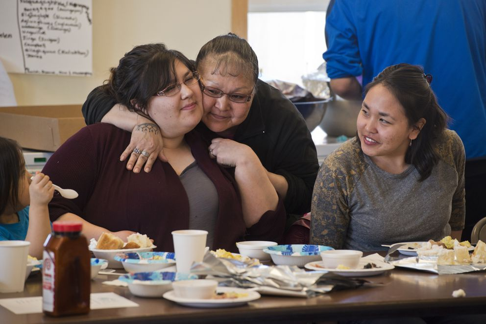Community health aide Danielle Reynolds, left, is hugged by Addie Pungowiyi. Brianne Gologergen, right, is also a health aide. The Native Village of Savoonga hosted a community appreciation dinner to honor Savoonga's seven community health aides on Thursday. (Marc Lester / Alaska Dispatch News)