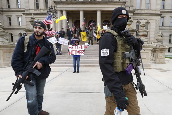 FILE - In this April 15, 2020, file photo protesters carry rifles near the steps of the Michigan State Capitol building in Lansing, Mich. Protesters drove past the Michigan Capitol to show their displeasure with Gov. Gretchen Whitmer's orders to keep people at home and businesses locked during the new coronavirus COVID-19 outbreak. (AP Photo/Paul Sancya, File)