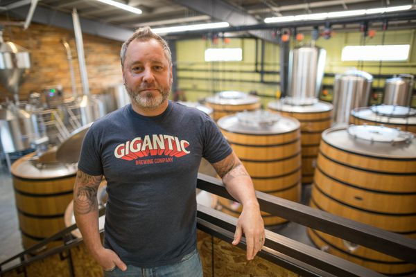 Anchorage Brewing owner Gabe Fletcher at his south Anchorage brewery Thursday, Nov. 2, 2017. Behind him are fouders, French oak fermentation barrels more commonly used for making wine. (Loren Holmes / Alaska Dispatch News)